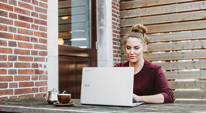 woman sitting outdoors using laptop