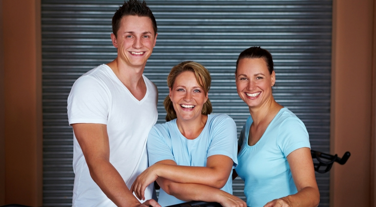 three gym people leaning on spin bike