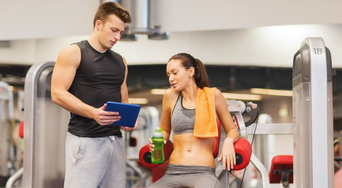 personal trainer helping gym member with automated gym software